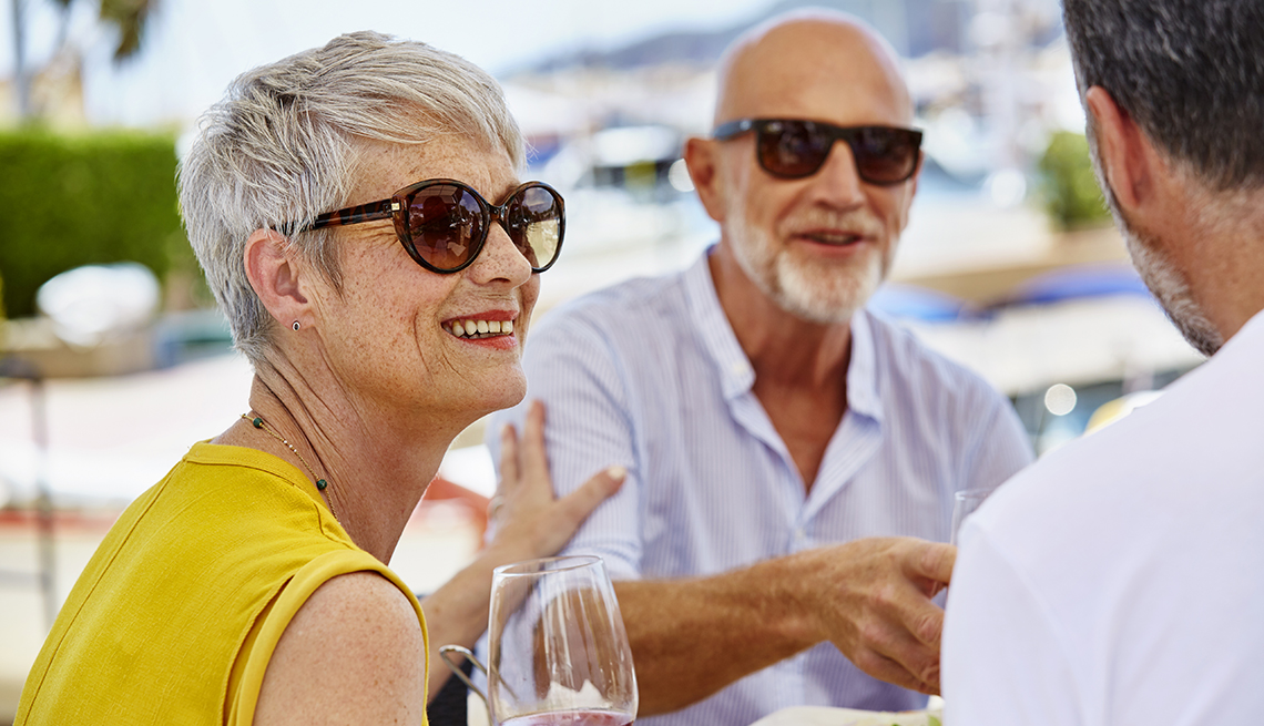 item 3 of Gallery image - A man and woman wearing sunglasses talking to a friend at a table at an outdoor restaurant