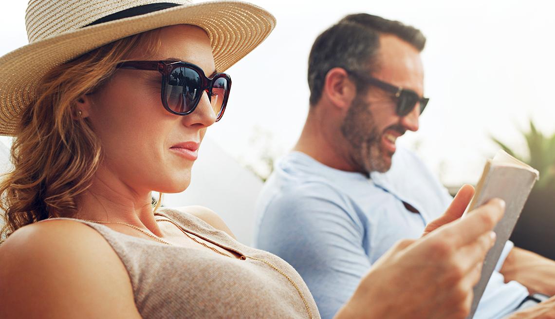 item 8 of Gallery image - Pareja sentada en sillas de playa con lentes de sol y mirando sus teléfonos móviles.