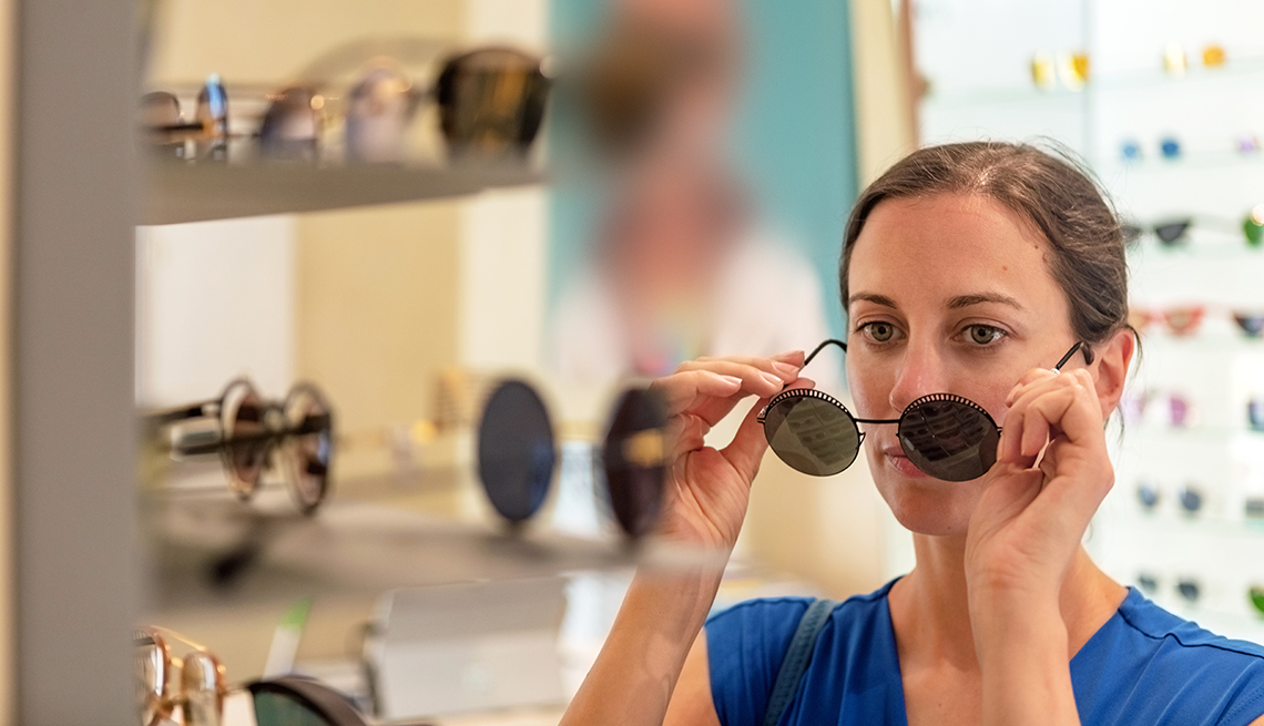 item 1 of Gallery image - A woman looking at a mirror in a store trying on sunglasses
