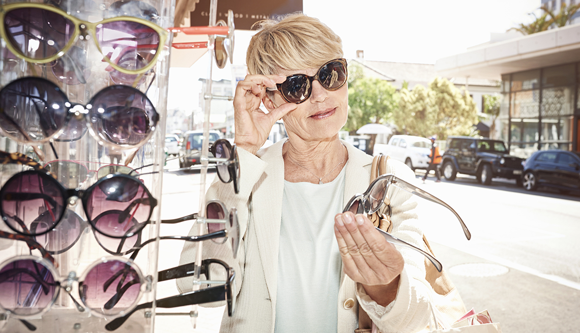 item 9 of Gallery image - A woman is trying on sunglasses and examining another pair in her hand