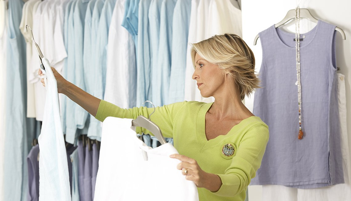A woman shopping in clothes shop comparing two tops on coathangers