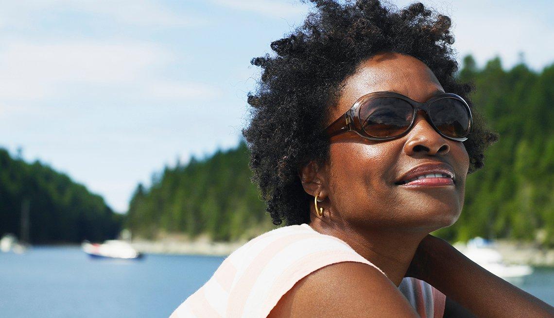 Mujer usando gafas frente a un lago.