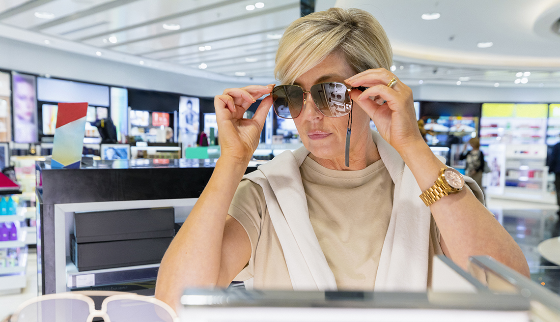 item 2 of Gallery image - A woman trying on a pair of sunglasses at a store in an airport