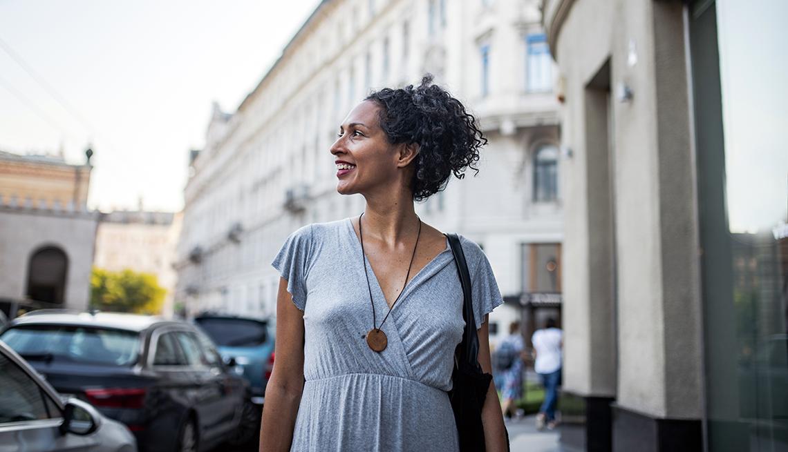 Mujer caminando por la calle en época de verano.