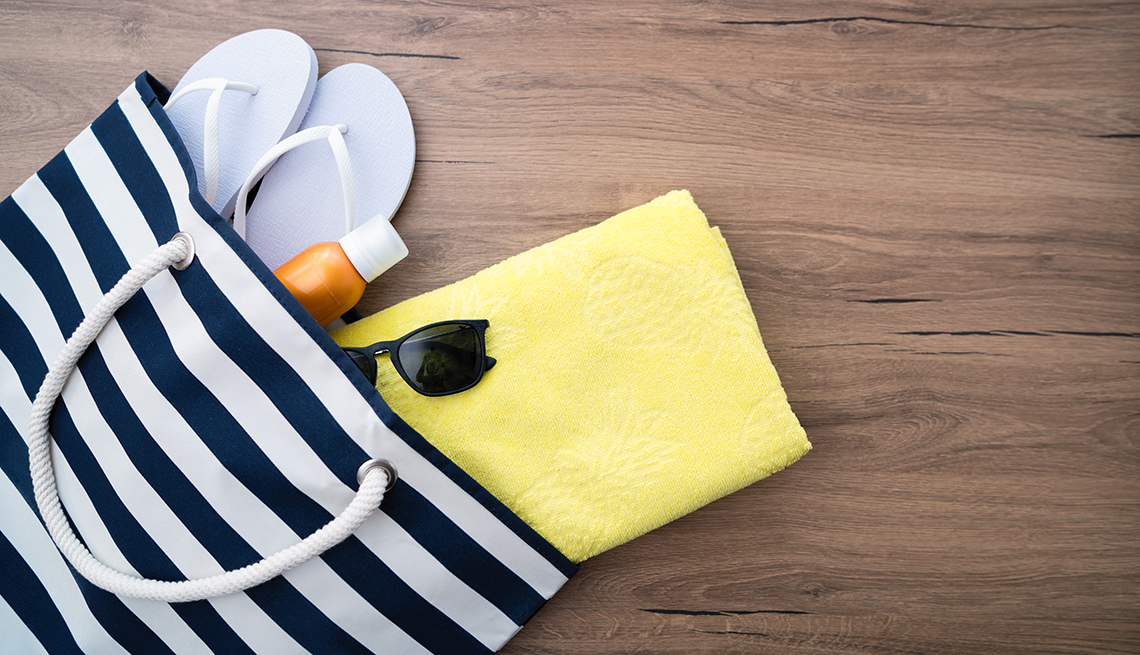 item 1 of Gallery image - Sandalias, loción, gafas de sol y una toalla en una bolsa de playa.