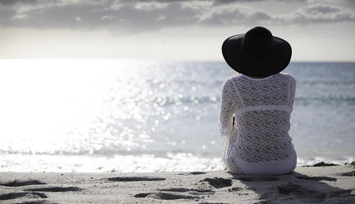 item 6 of Gallery image -  una mujer sentada en la playa durante el atardecer
