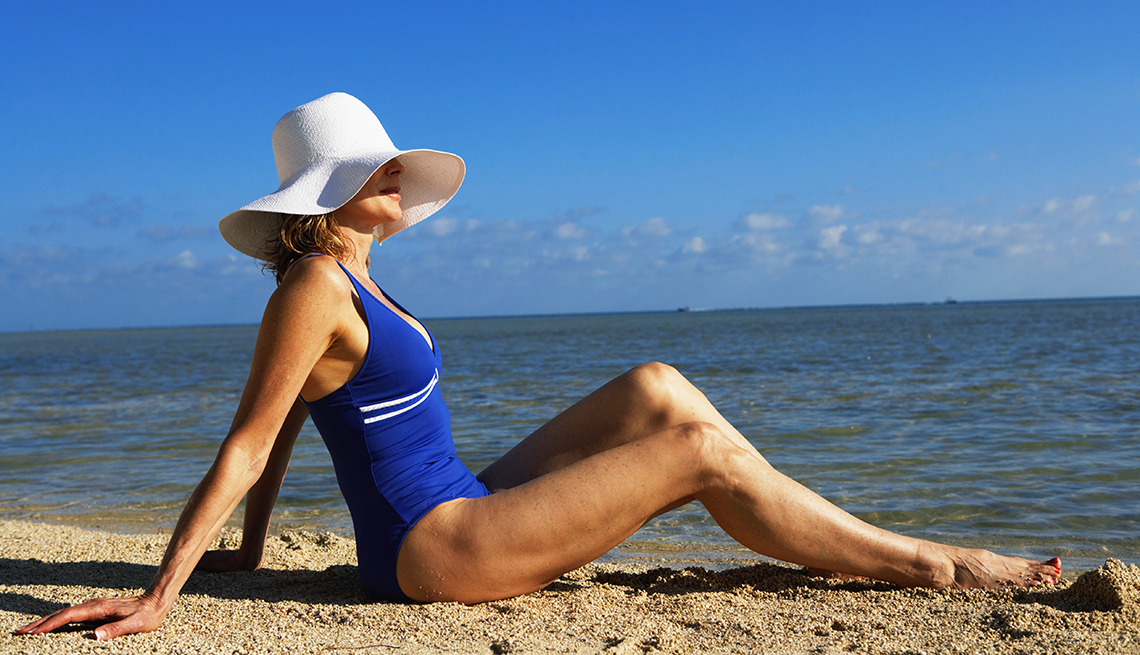 item 9 of Gallery image - Una mujer sentada en la arena en la playa.