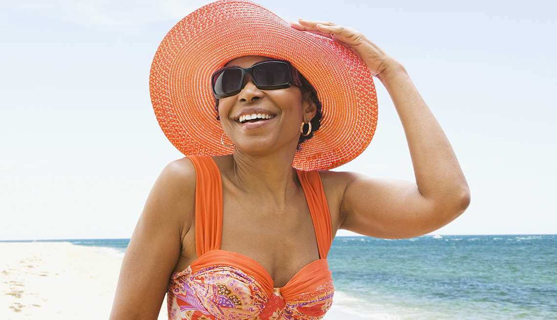 A woman in a bathing suit and hat at the beach