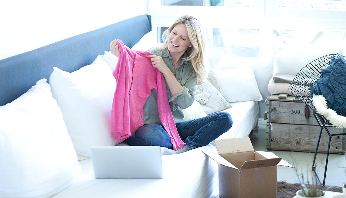 A woman looking at a clothing item on her couch