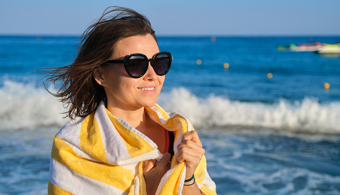 item 5 of Gallery image - A smiling woman wearing sunglasses at the beach