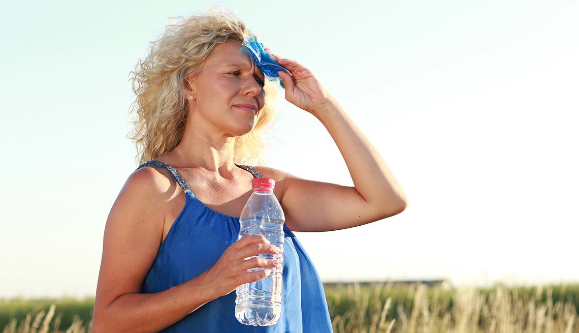 A woman wiping her forehead with a paper tissue while holding a water bottle outside