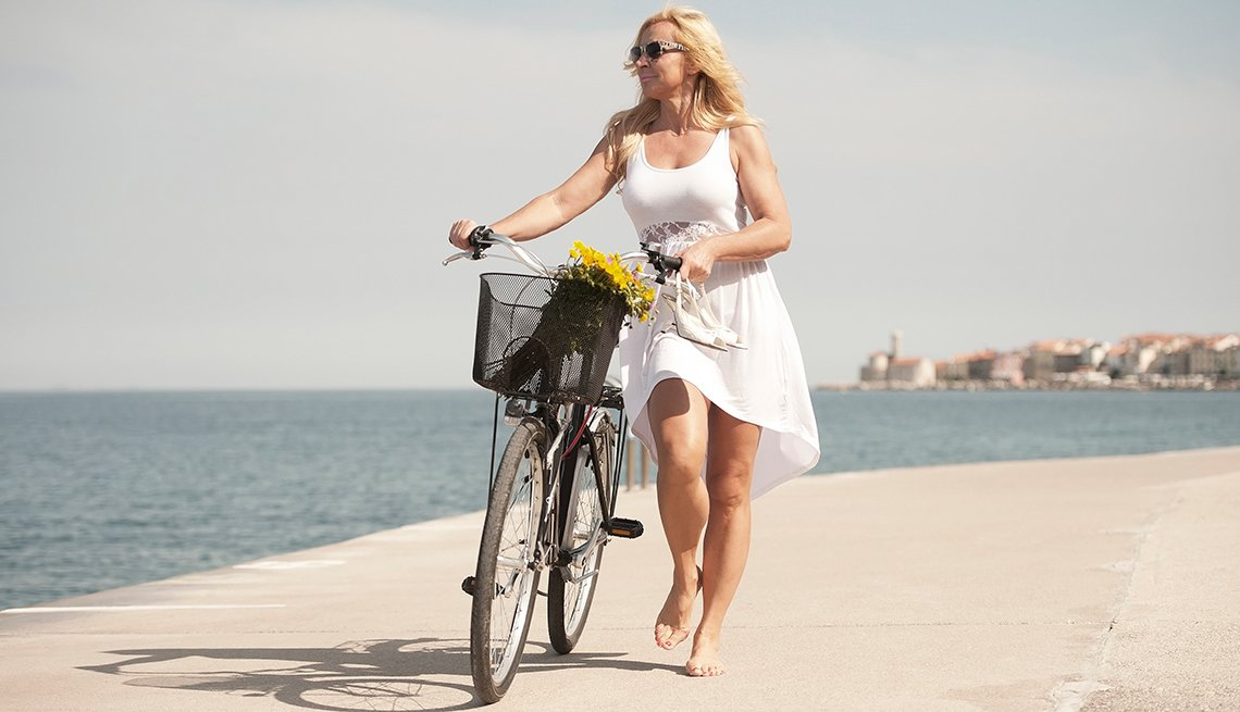 A woman walking with her bicycle on the pavement nearby the water