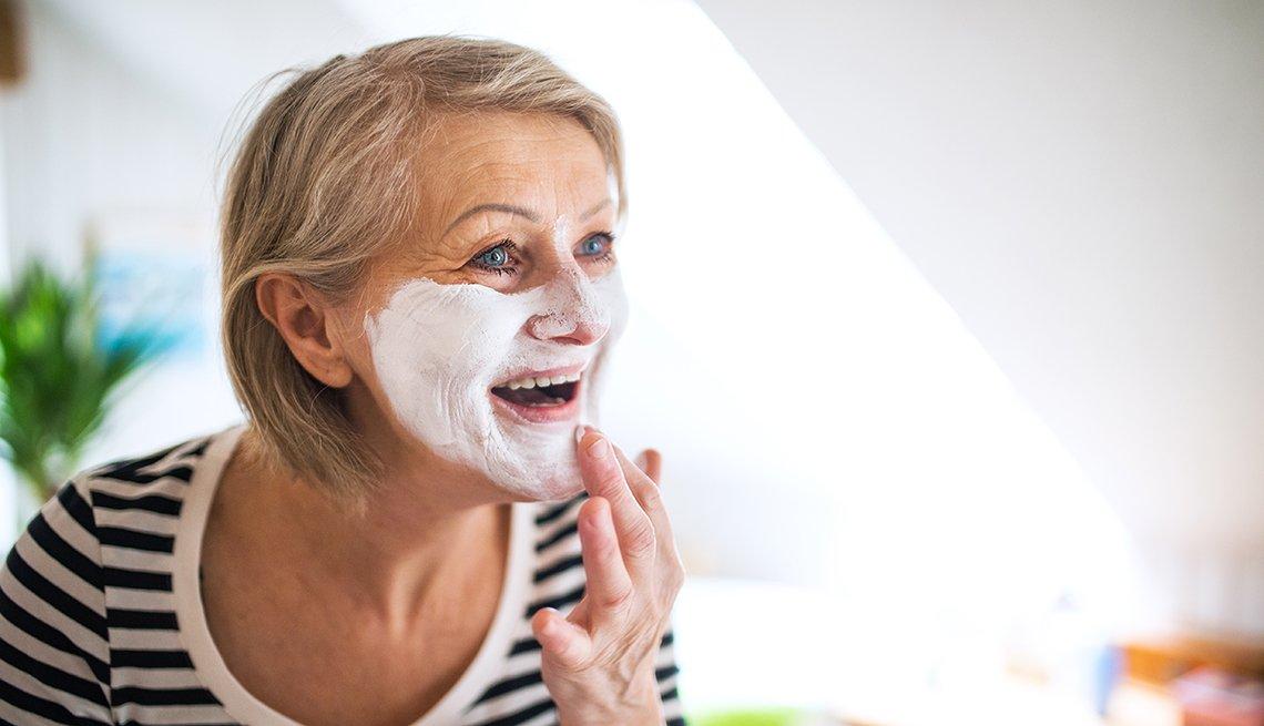 Mujer aplicándose una crema en la cara.