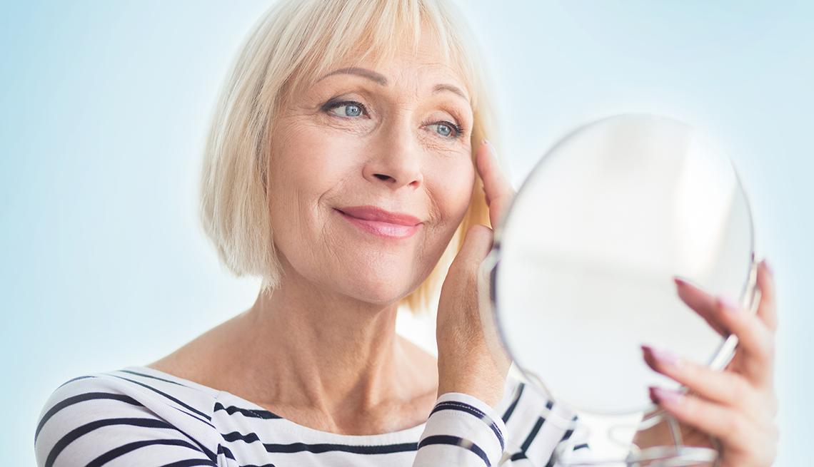 una mujer examina su rostro en un espejo de mano
