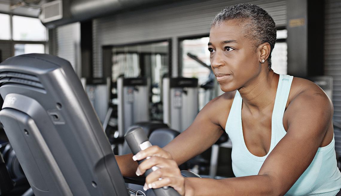 item 9 of Gallery image - Una mujer con una bicicleta estática en el gimnasio.
