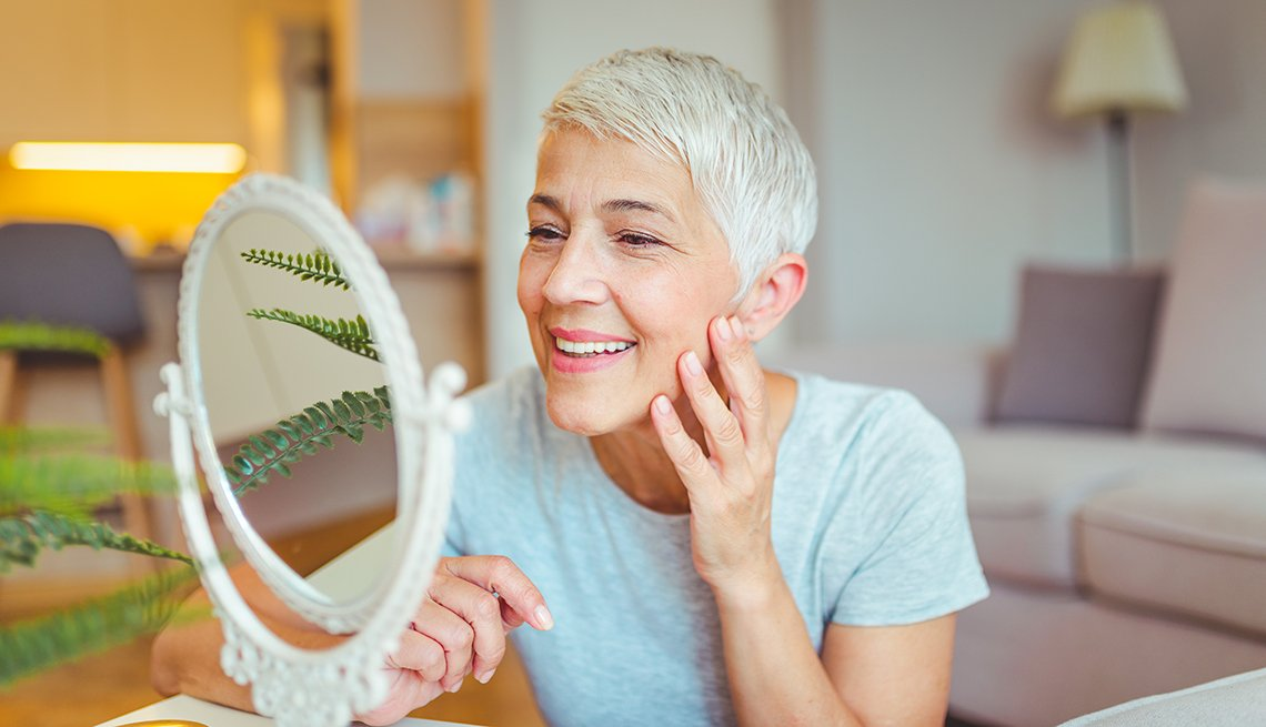 A woman examining her face in a mirror