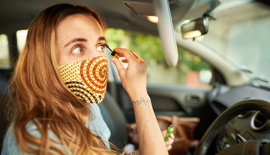 A woman wearing a face mask is applying makeup sitting in the driver seat of her car