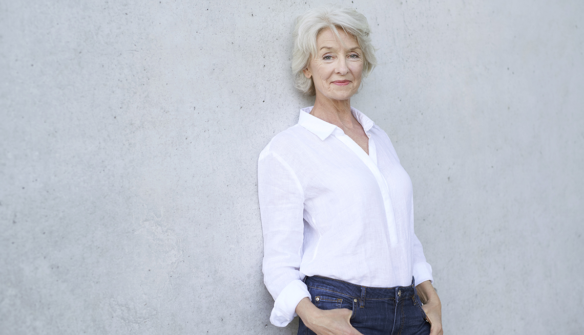 A woman wearing a white button-down shirt leaning against a concrete wall