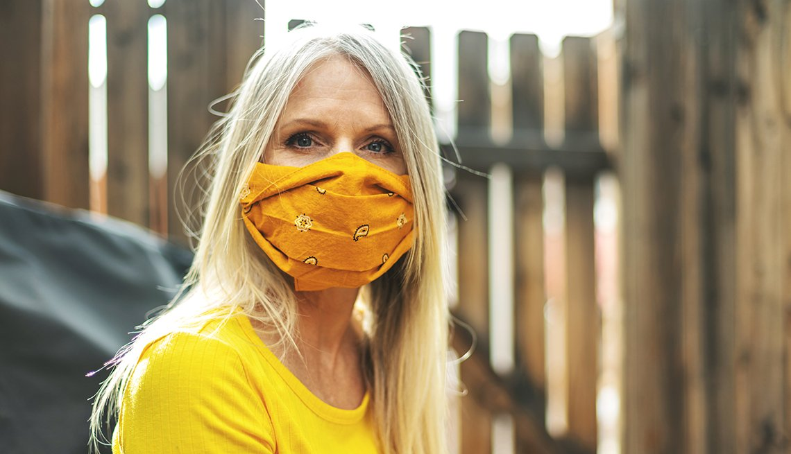 A woman wearing a yellow orange face mask