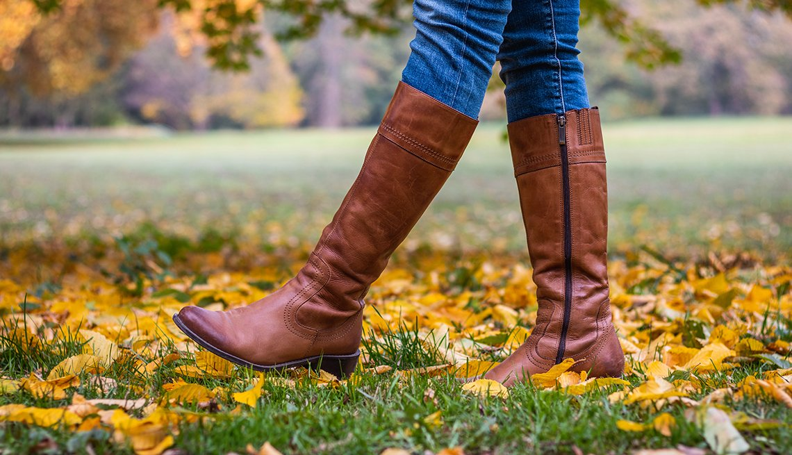 A woman walking in brown tall boots in the leaves and grass at a park during the autumn