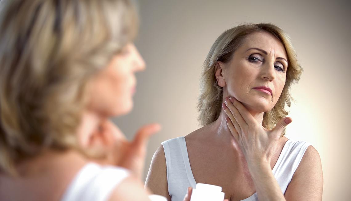 item 10 of Gallery image - Mujer aplicándose una crema en el cuello.