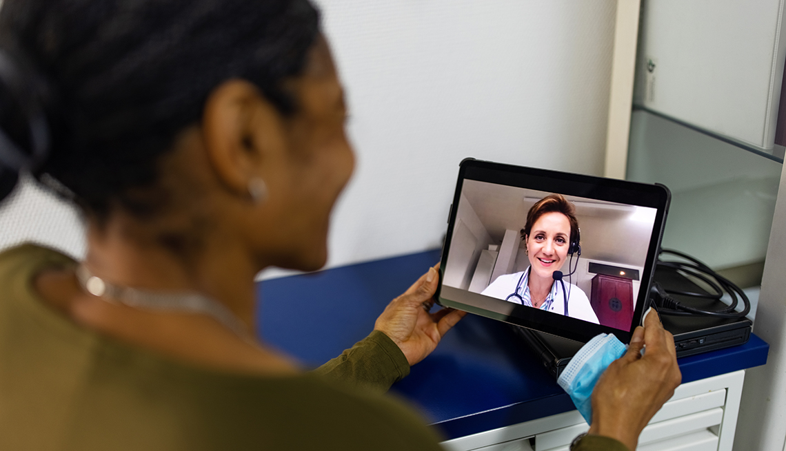item 11 of Gallery image - A woman using a tablet to have a telehealth video conferencing appointment with a doctor