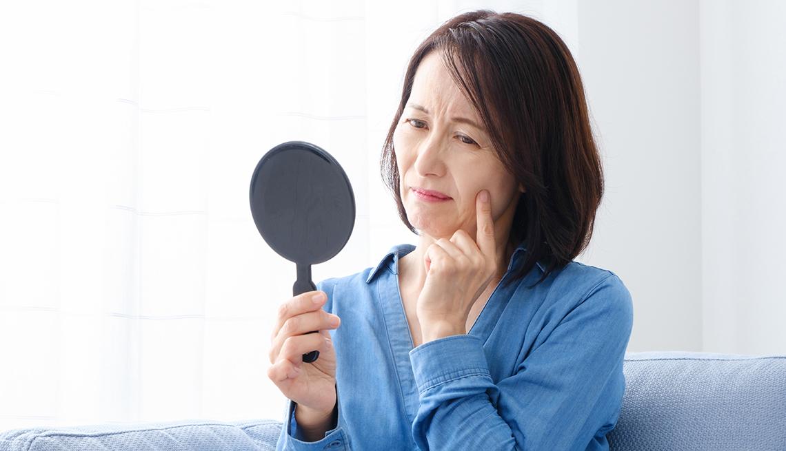 Mujer mirándose en un espejo que sostiene en su mano