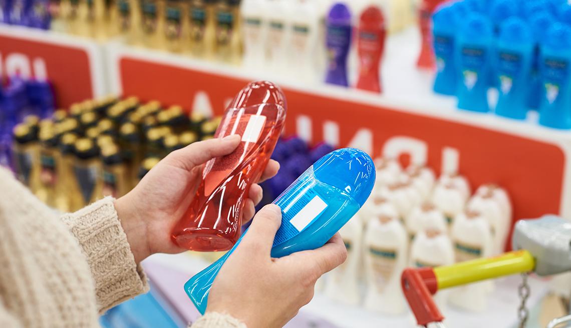 Una mujer sosteniendo dos botellas de champú dentro de una tienda.