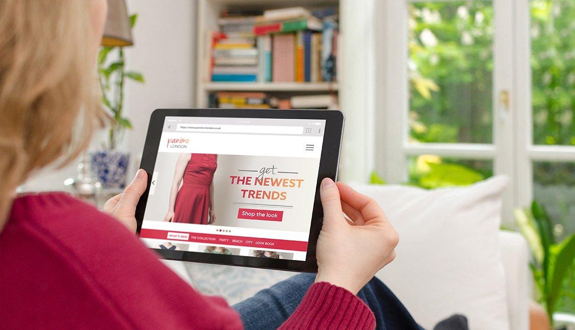 Mujer mirando ropa en una tableta en la sala de su casa.