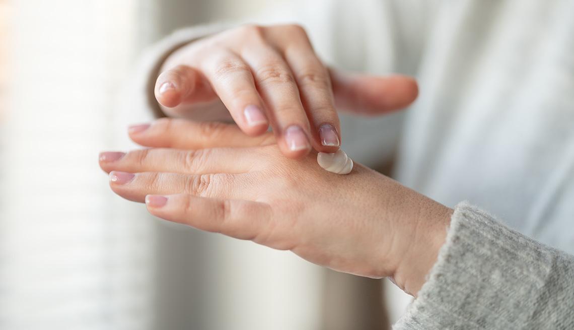 Mujer aplicándose crema en las manos.