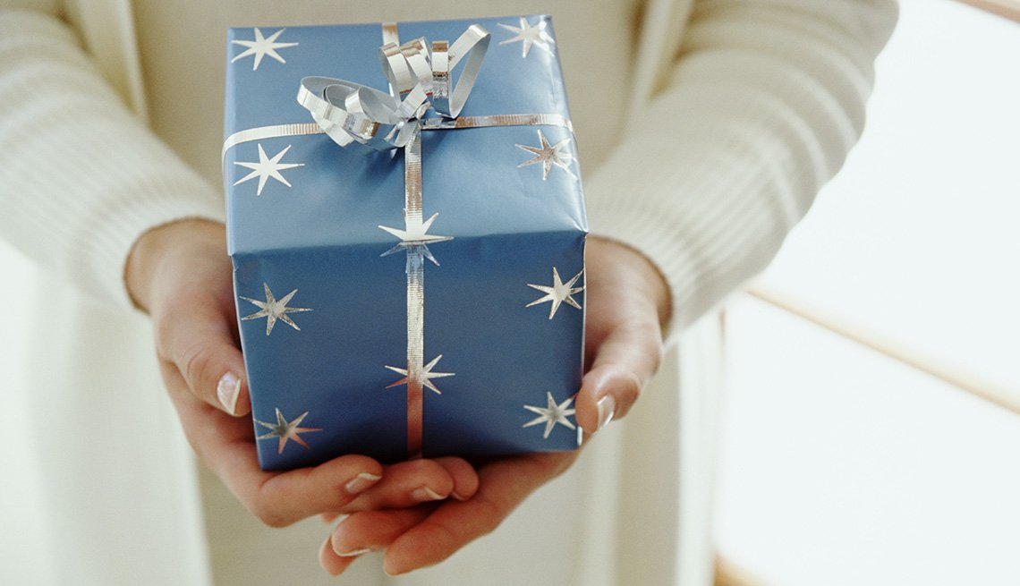 A closeup of a woman holding a blue wrapped gift box