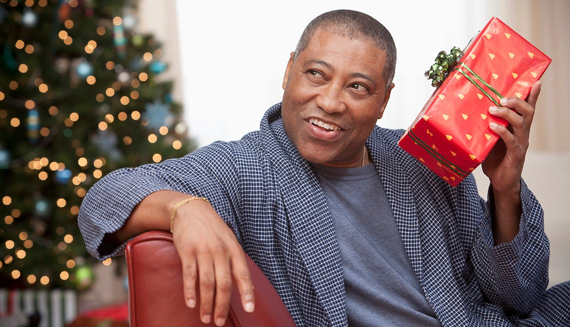 A man holding and shaking a holiday gift