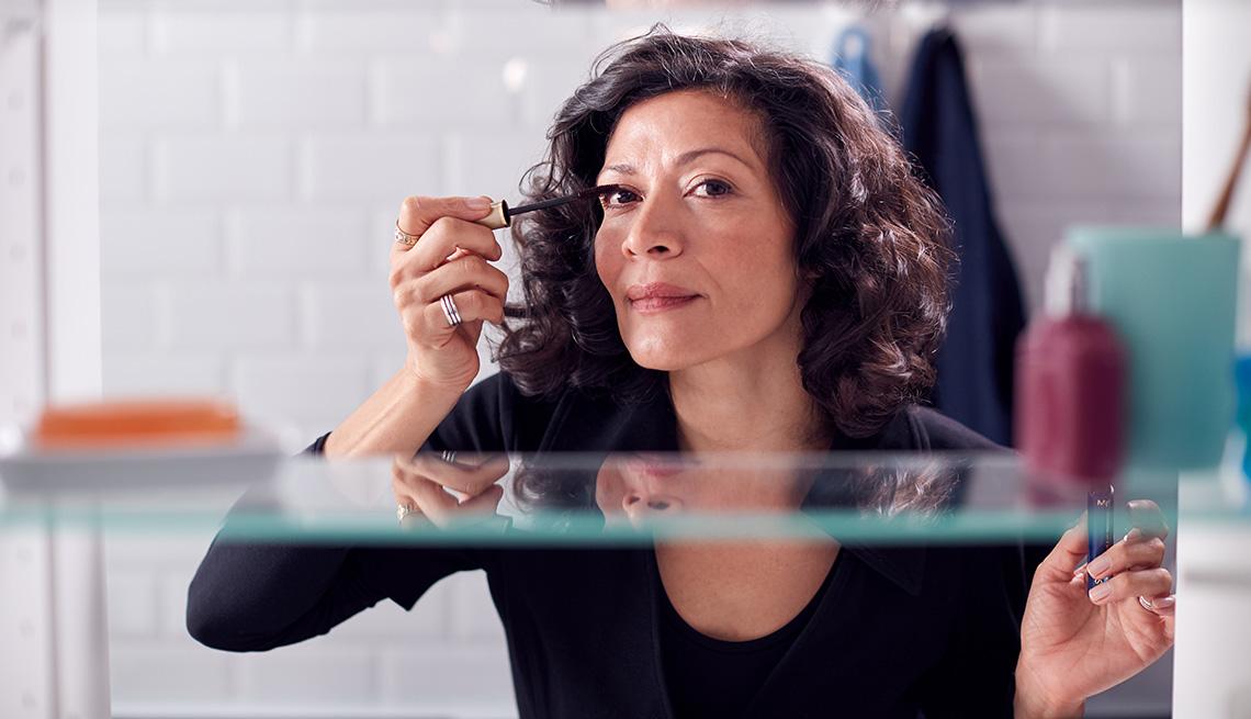 A view through a bathroom cabinet of a woman applying mascara