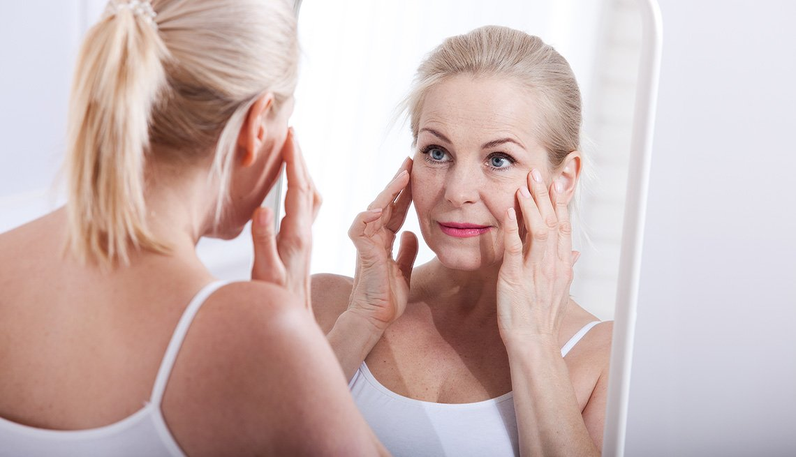 item 1 of Gallery image - A woman looking at her face in a mirror