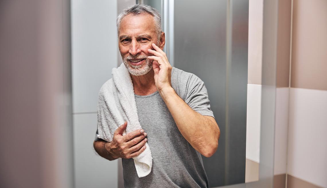 Un hombre se toca su rostro mientras se mira en el espejo del baño.