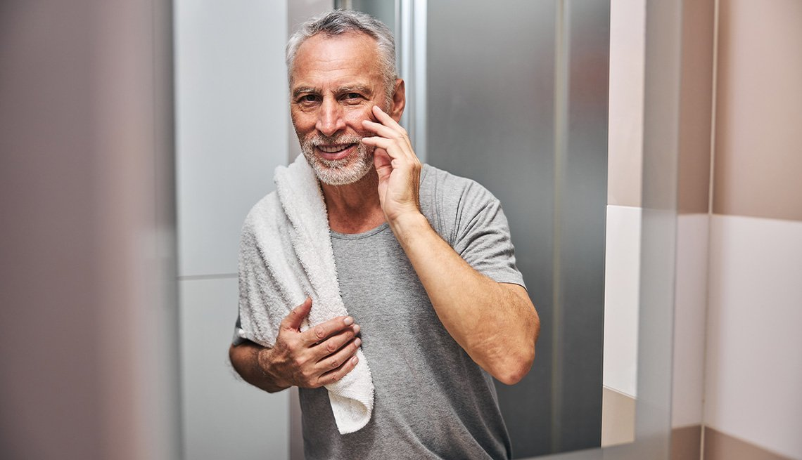 A man touches his face while looking at the bathroom mirror