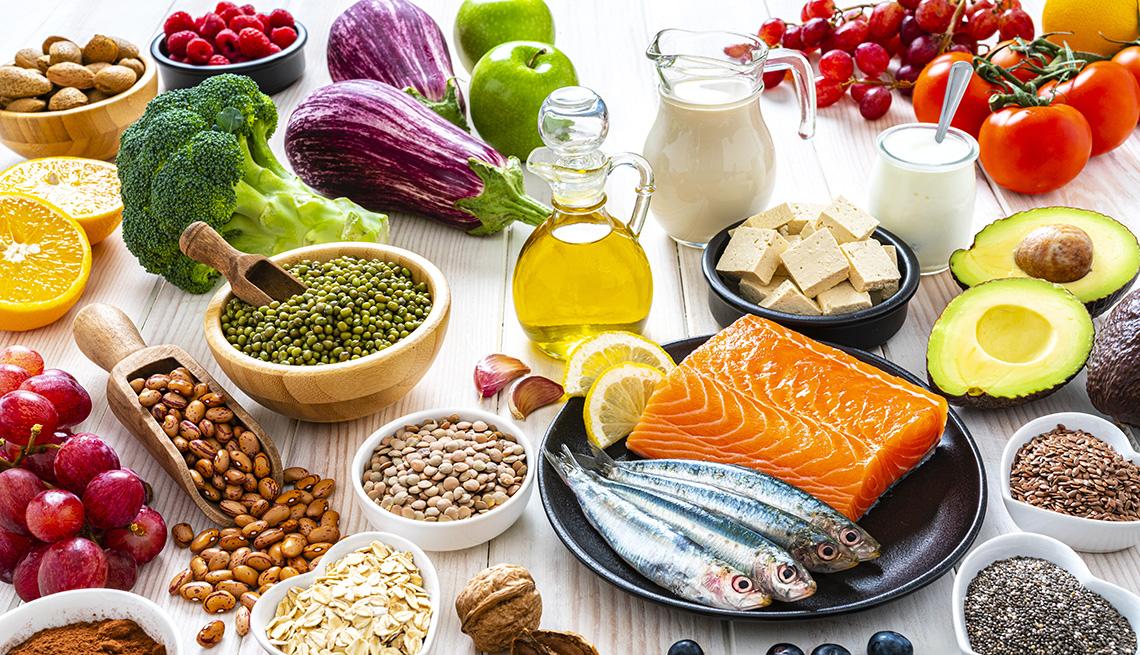 item 9 of Gallery image - Una variedad de alimentos mostrados en una mesa que incluyen frijoles, pescado, frutas, verduras, leche y aceite de oliva.