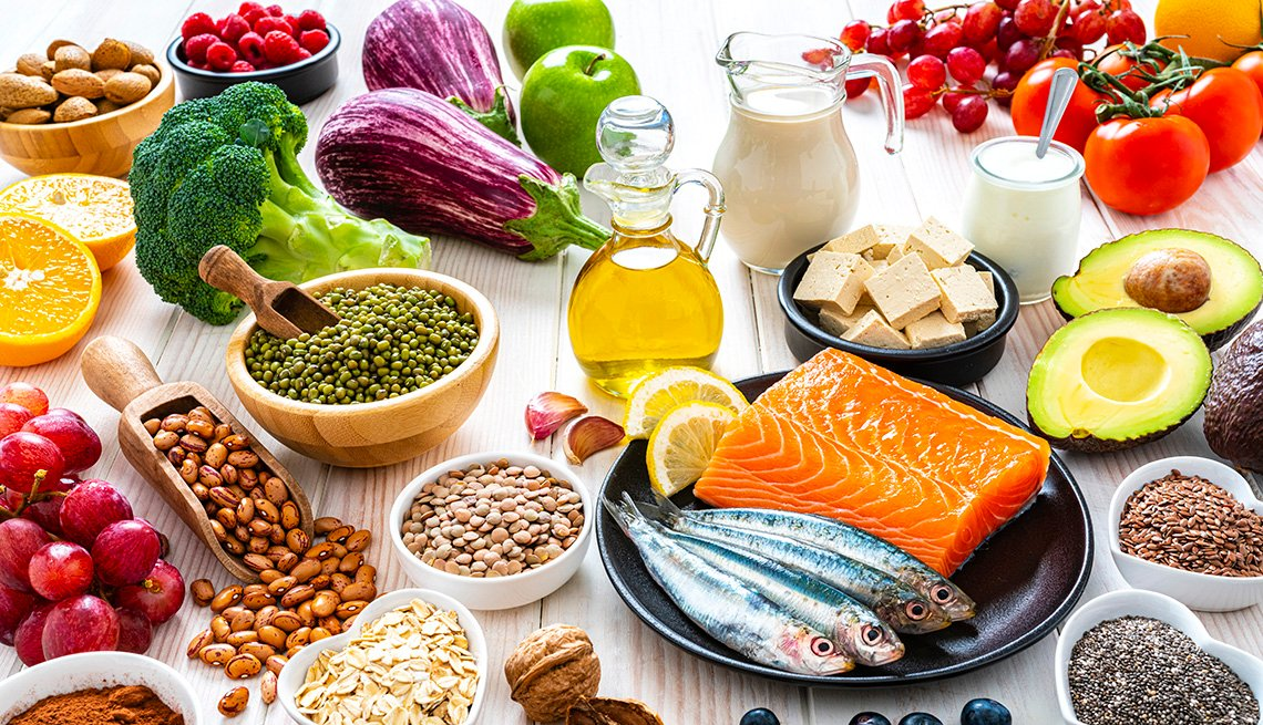item 9 of Gallery image - A variety of foods displayed on a table that include beans, fish, fruits, vegetables, milk and olive oil