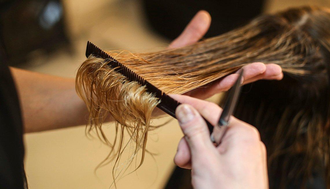 Un primer plano de una persona cortando el cabello de una mujer en una peluquería.
