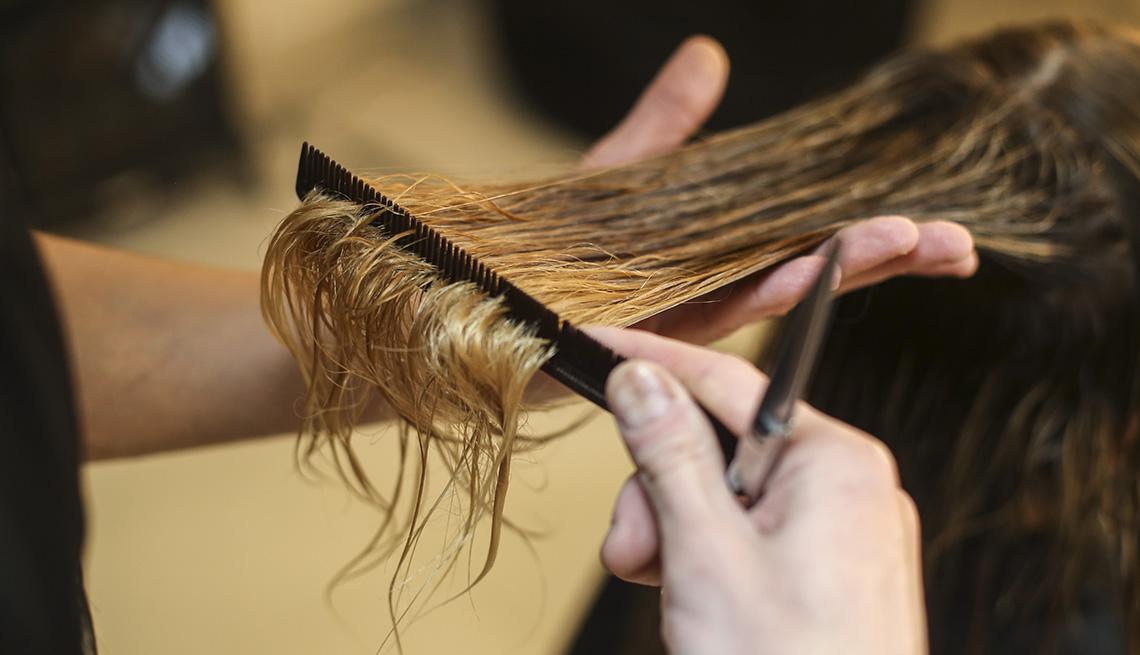 A closeup of a person cutting a woman's hair in a hair salon