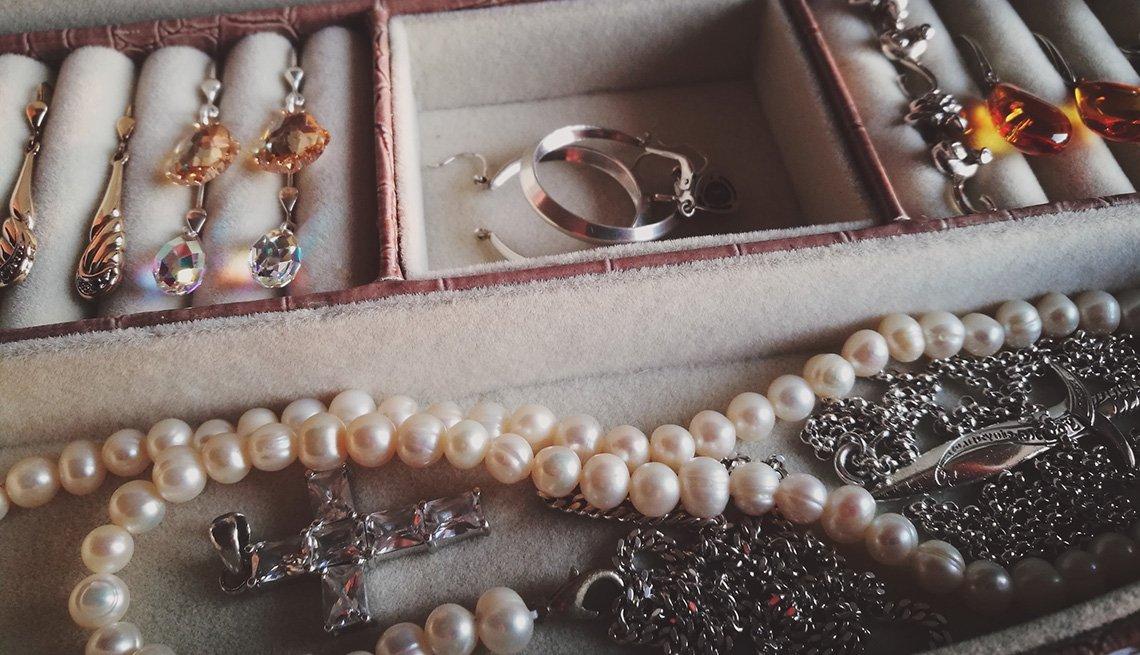 Pendientes, collares y otras joyas acomodadas en una caja.