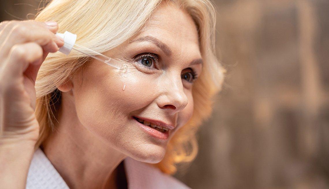 Mujer aplicando suero facial.