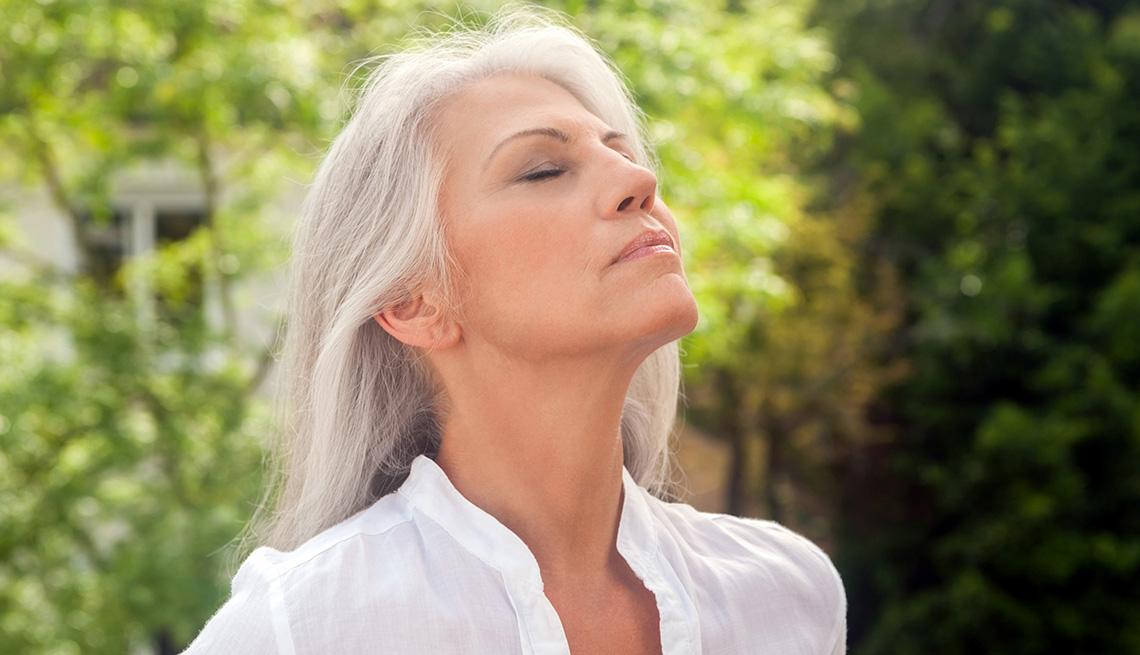 Una mujer con la barbilla levantada disfrutando del aire libre.