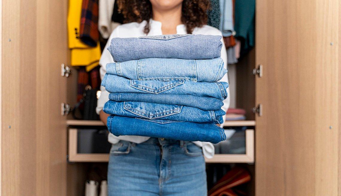 Una mujer de pie delante de un armario sosteniendo una pila de jeans doblados.