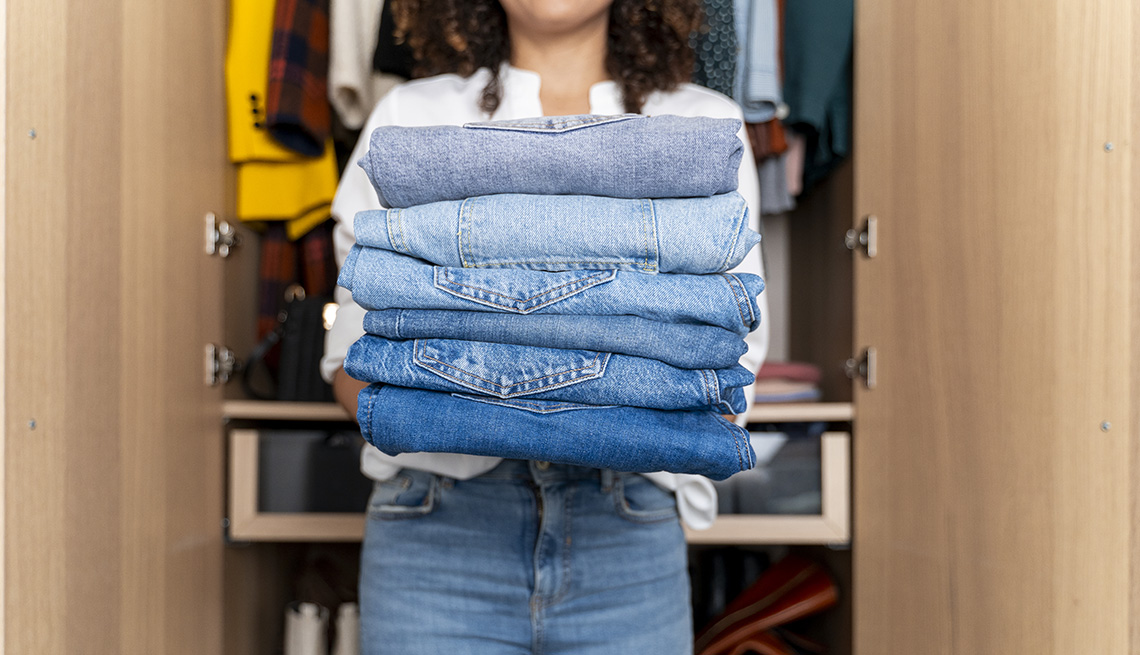 A woman standing in front of a wardrobe closet holding a stack of folded jeans