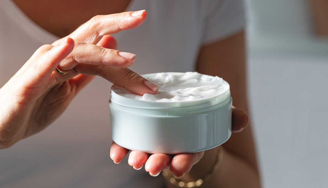 item 10 of Gallery image - A close-up of woman's hands holding moisturizing cream jar