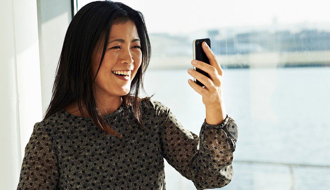 item 11 of Gallery image - Una mujer en una videollamada en su teléfono celular.