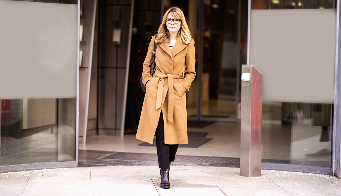 A woman walking out of a building wearing a beige trench coat