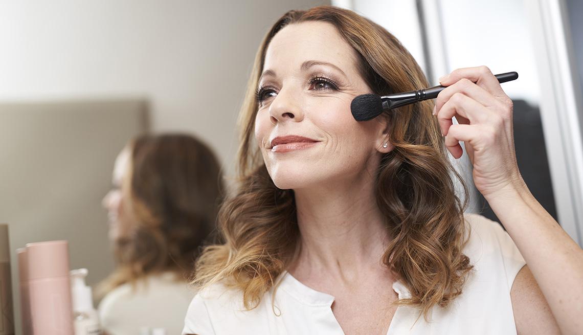 Una mujer maquillándose delante de un espejo.