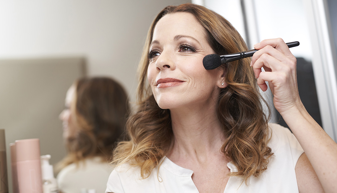 A woman applying makeup in front of a mirror